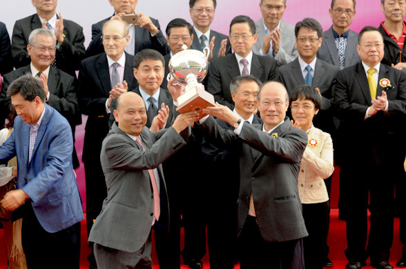 """Trainer Joe Lau (left) is presented the trophy by CEO of SJM Dr Amrose So after """"The Alfonso"""" won the 2015 Macau Derby"""