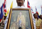 A well-wisher holds a picture of Thailand's King Bhumibol Adulyadej as he joins anti-government protesters gathering outside the Grand Palace on Coronation Day in Bangkok May 5, 2014. Thousands of anti-government protesters marched to the historical part of Bangkok to show their loyalty to the revered King Bhumibol on the 64th anniversary of his coronation. REUTERS/Damir Sagolj (THAILAND - Tags: ROYALS ANNIVERSARY CIVIL UNREST) - RTR3NULS